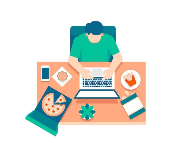 Een man werkt op een laptop vanuit bovenaanzicht omringd door voedsel en snacks