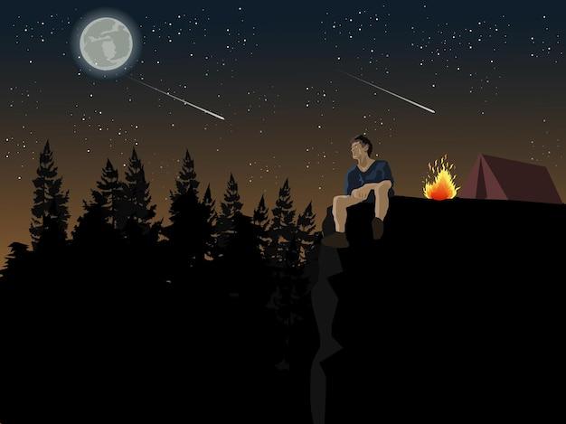 Een man zit op een klif naar de maan te kijken. hij kampeert in een dennenbos met een blauwe lucht en sterren op de achtergrond.