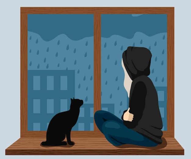 Een meisje met een kat zit op de vensterbank en kijkt naar de regen buiten het raam het meisje is verdrietig