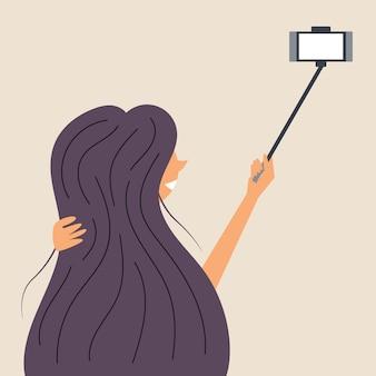Een meisje met lang haar wordt gefotografeerd op een selfiestick