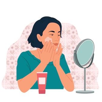 Een meisje voor een tafelspiegel smeert crème op haar gezicht