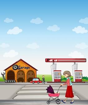 Een moeder die langs een garage en een benzinestation loopt