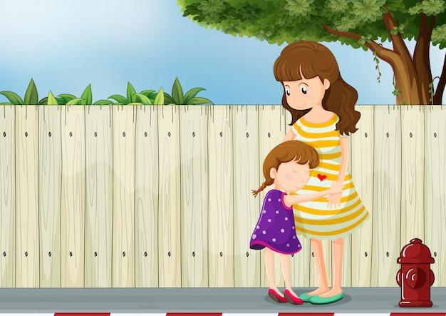 Een moeder en haar dochter bij het hek op de weg