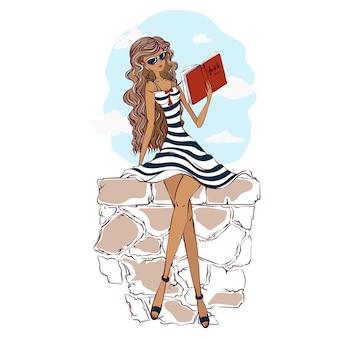 Een mooi meisje in een gestreepte lichte zomerjurk en zonnebril zit op een stenen borstwering en leest een boek.