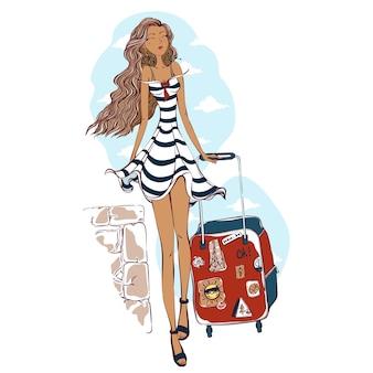 Een mooi meisje in een zomerse gestreepte zomerjurk draagt een reistas met reisstickers.