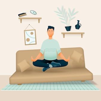 Een ontspannen glimlachende man zit in zijn kamer of appartement op een zachte bank met zijn benen gekruist en mediteert.