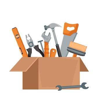 Een open kartonnen doos in een pakket met een set gereedschappen van een bouwer en een huisschilder erin