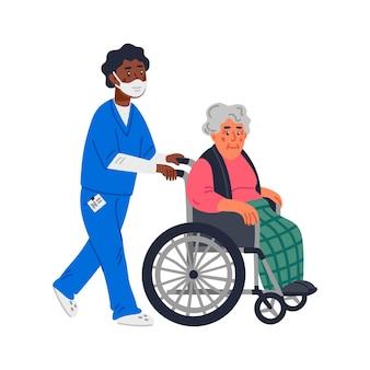 Een oudere vrouw in een rolstoel en een verpleger met een gezichtsmasker