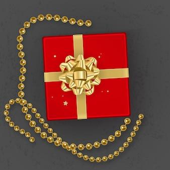 Een realistische rode geschenkdoos versierd met een gouden strik, bovenaanzicht.
