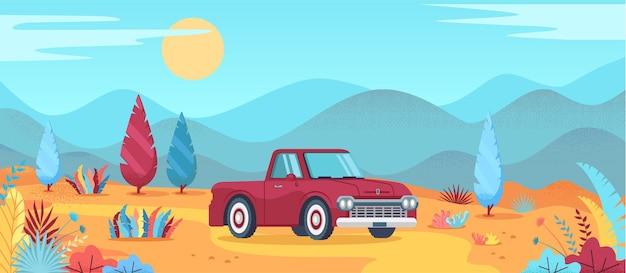 Een rode oude auto rijdt op een weg door de woestijnheuvel