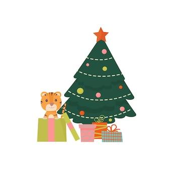 Een schattig klein tijgerwelpje zit in een doos bij de kerstboom met cadeautjes