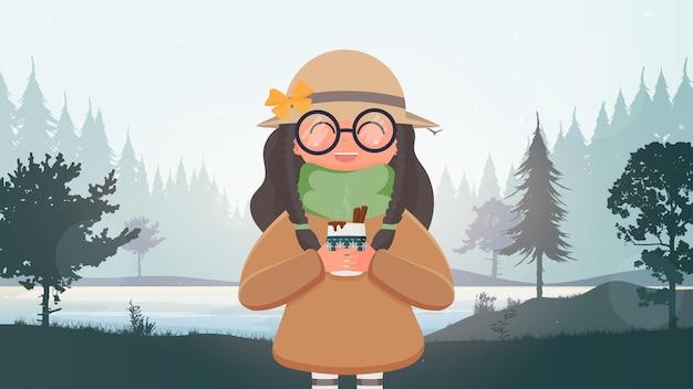 Een schattig meisje in een hoed en bril houdt een kopje met een warme drank.