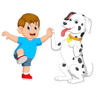 Een schattige hond speelt met zijn baasje en houdt zijn hand vast