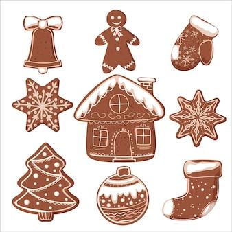 Een set van verschillende peperkoek kerstkoekjes met glazuur. bel, man, huis, sok, sneeuwvlokken, boom, bal en want.