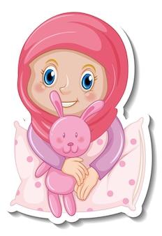 Een stickersjabloon met een moslimmeisje knuffelt een kussen en een konijnenpop