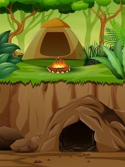 Een tent met kampvuur boven een ondergrondse grot