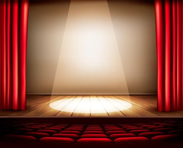 Een theaterpodium met een rood gordijn, stoelen en een spotlight.