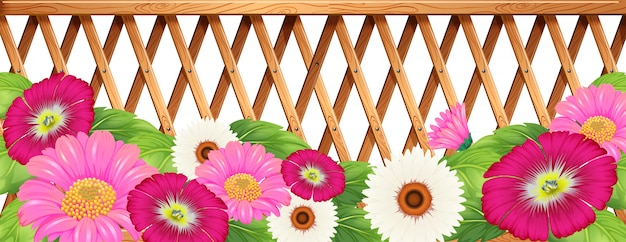 Een tuin met bloemen met een hek