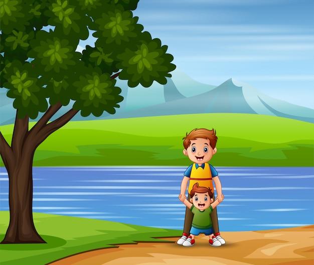 Een vader en zoon wandelen langs het meer