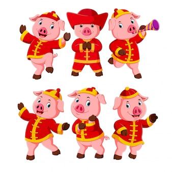 Een verzameling van kleine roze varkens gebruikt een chinees nieuwjaarskostuum