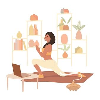 Een vrouw die thuis yoga beoefent. bekijk online lessen op een laptop en gebruik de aromalamp tijdens yoga.