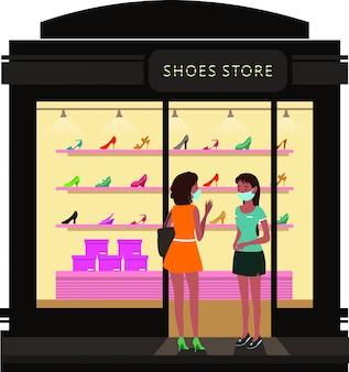 Een vrouw in gesprek met de verkoopster bij schoenenwinkel