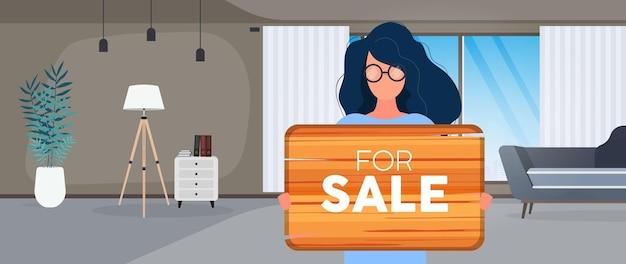 Een vrouw met een bril houdt een houten bord vast met het opschrift te koop. jonge vrouw met een houten bord. het concept van de verkoop van een appartement, kantoor of gebouw. vector.