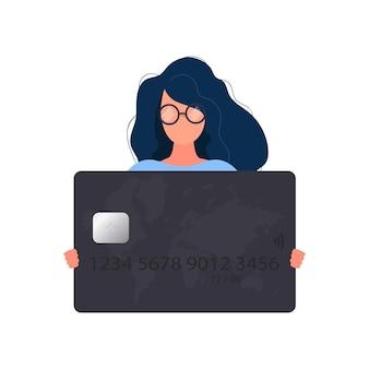 Een vrouw met een bril houdt een zwarte bankkaart vast. jonge vrouw met een plastic kaart voor een atm-machine geïsoleerd op een witte achtergrond. vector.