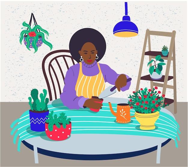 Een vrouw met een zwarte huid zorgt voor kamerplanten