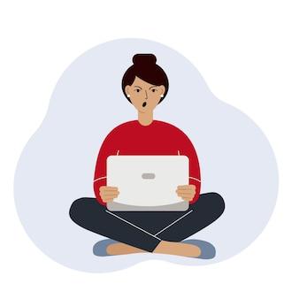 Een vrouw of een meisje zit en werkt op een laptop. werken op afstand of communicatie via internet. boos, geïrriteerd.