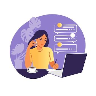 Een vrouw werkt op een laptopcomputer en praat aan de telefoon zittend aan een tafel thuis met een kopje koffie en papieren.