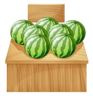 Een watermeloentribune met een leeg houten uithangbord