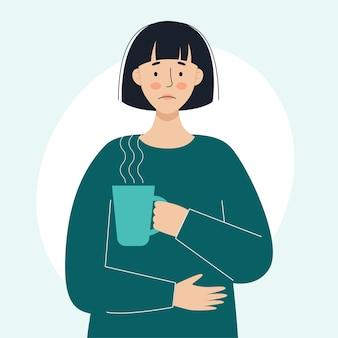 Een zieke vrouw houdt een mok met een hete medicinale drank in zijn hand het concept van zieke mensen