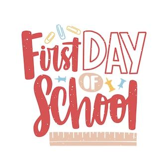 Eerste dag van school belettering geschreven met kalligrafisch lettertype en versierd met paperclips, punaises en liniaal verspreid rond.