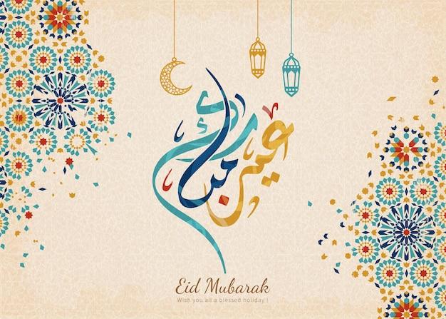 Eid mubarak-kalligrafie betekent prettige vakantie met prachtige blauwe arabeskpatronen en hangende lantaarns Premium Vector