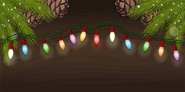 Elektrische kerstboomslinger met veelkleurige bollen voor kerstdesign. gloeiende elektrische garland en vuren takken met dennenappels op een houten achtergrond.