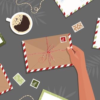 Envelop in de hand op tafelachtergrond, met de hand getekende brieven en ansichtkaarten op werkruimte