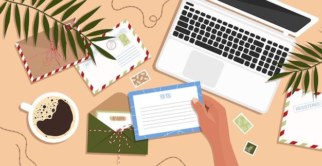 Enveloppen, brieven, ansichtkaarten en een laptop op tafel. envelop in de hand.