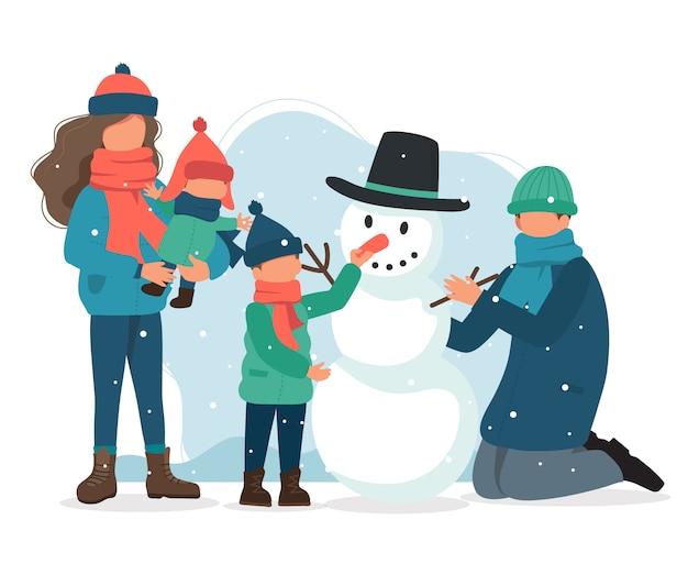 Familie die een sneeuwman in de winter maakt.