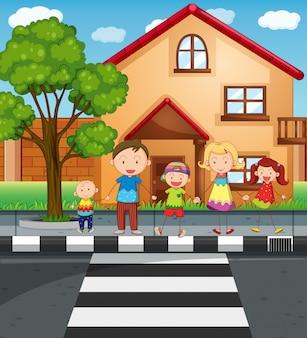 Familie hand in hand tijdens het oversteken van de weg
