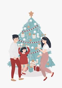 Familie met een kind danst in de buurt van de kerstboom