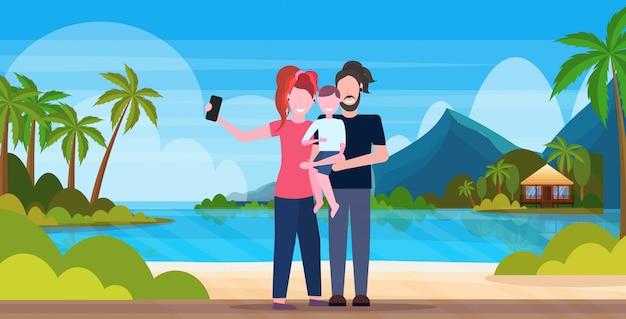 Familie op strand selfie foto nemen op smartphone camera zomervakantie concept moeder vader en zoon permanent tropisch eiland kust achtergrond volledige lengte horizontaal