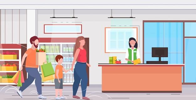 Familie winkelen in de moeder en zoon van de supermarkt de te zware vader die voor aankoop bij de binnenlandse vlakke volledige volledige lengte van de controleteller kruidenierswinkel betalen
