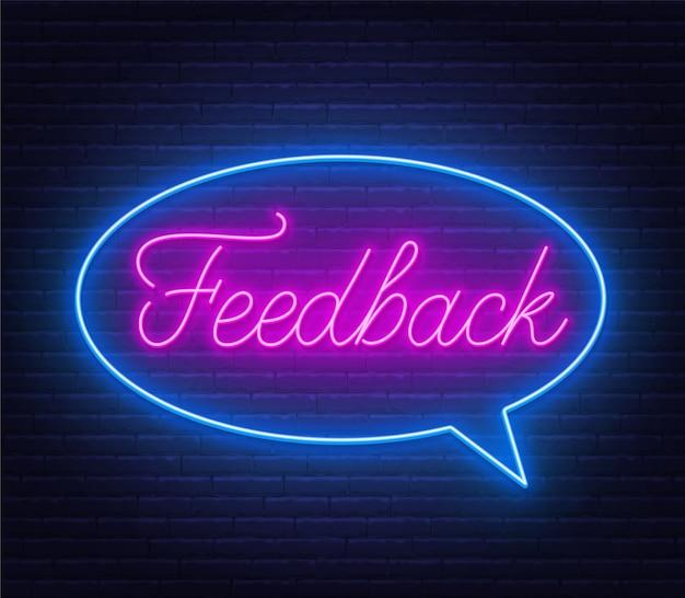 Feedback neonreclame in tekstballon frame op bakstenen muur achtergrond.