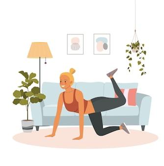 Fitness jonge vrouw doet gymnastiek in de woonkamer.
