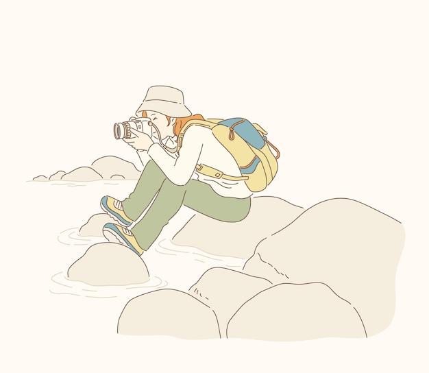 Fotograafmeisje dat dichtbij rivierrots in lijntekeningen zit