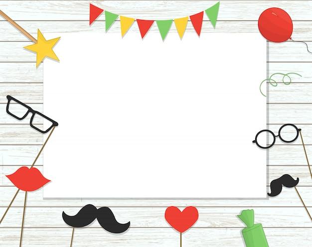 Fotohokje rekwisieten op stok, ballonnen, confetti, cadeautjes, snoepjes op armoedige houten achtergrond met plaats voor tekst
