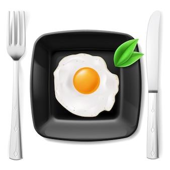 Gebakken ei op zwarte plaat geserveerd met mes en vork