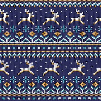 Gebreid naadloos ornament met lopende herten op een blauwe achtergrond.