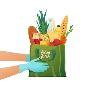 Gehandschoende handen houden een katoenen boodschappentas met boodschappen vast. eco-pakket met eten uit de winkel.